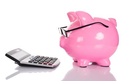 Piggy bank wearing glassing looking at a calculator